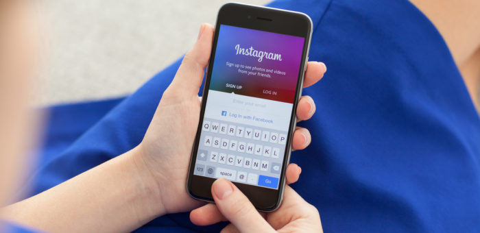 Woman holding cell phone with Instagram pulled up