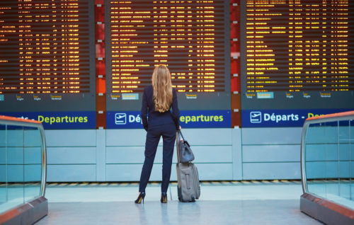 Young woman looking at travel board
