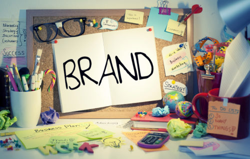 Brand word on paper pinned on cork bulletin board in a messy office.