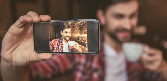 man taking selfie with coffee