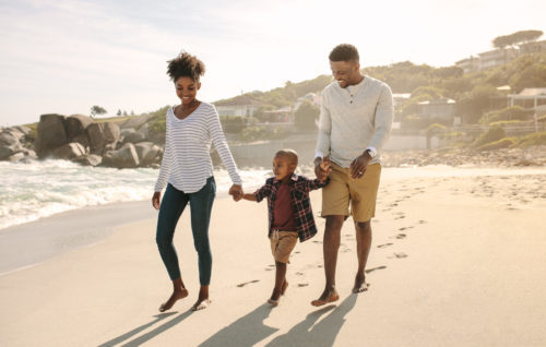 Parents holding hands of son and walking on beach.