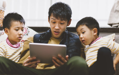 A father is reading stories on a digital tablet to his sons at home.
