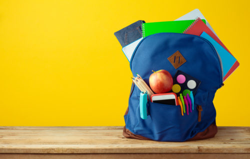 School bag backpack with notebooks, smart phone and pencils over yellow background.