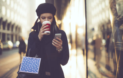 Woman walking down city street sipping coffee and looking at phone