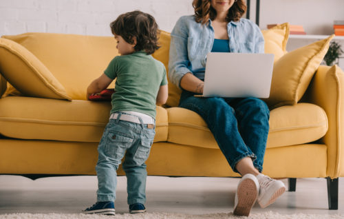 kid standing near sofa while mother working with laptop