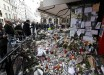 People look at flowers, candles and messages in tribute to victims in front of the La Belle Equipe cafe, one of the sites of the deadly attacks in Paris