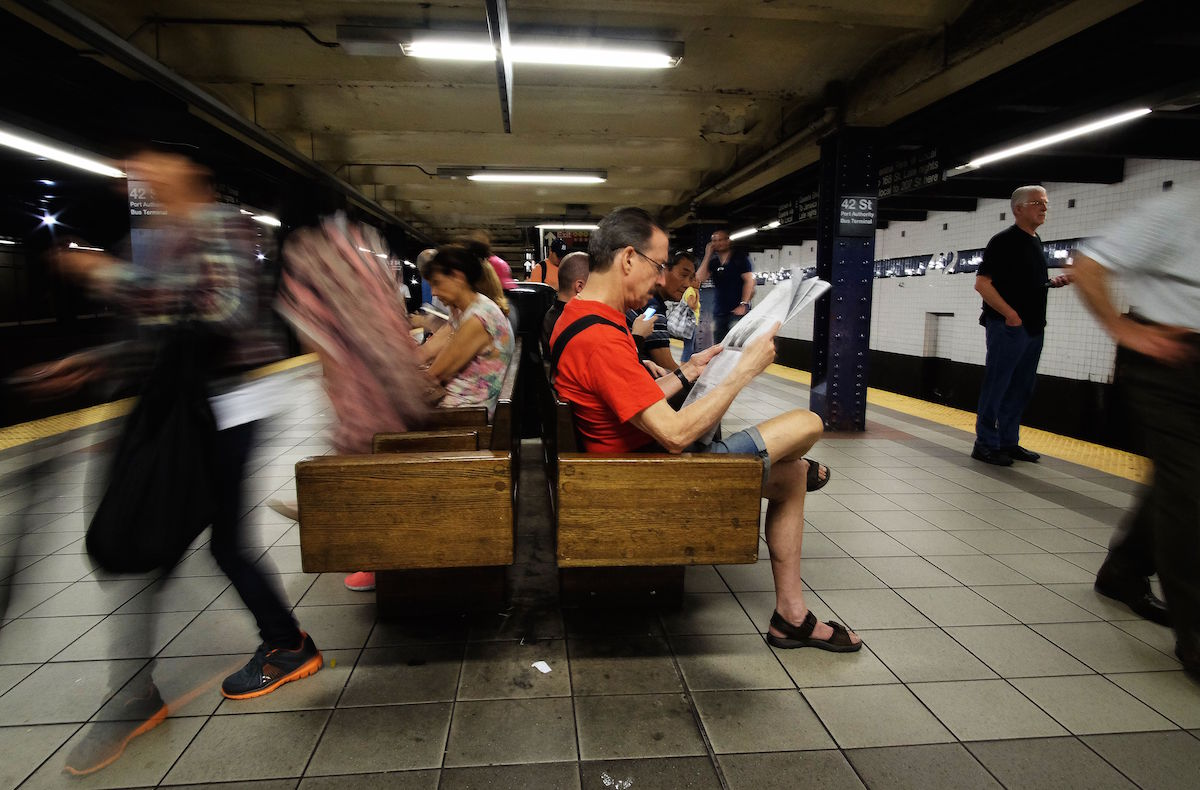 A commuter (R) reads a newspaper as he waits for a train in a subway station in New York on July 1, 2015. Photo credit should read JEWEL SAMAD/AFP/Getty Images