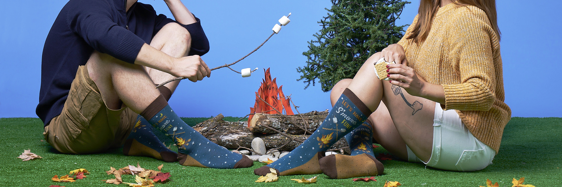 Two people wearing socks with s'mores on it sitting around a fake camp fire with marshmallows on sticks.