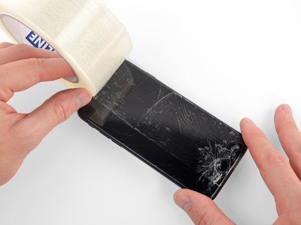 Déposer des bandes de ruban adhésif transparente sur l'écran de l'iPhone en les faisant se chevaucher jusqu'à ce que la surface soit complètement recouverte.