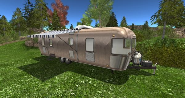 A retro-style silver camper in the forest