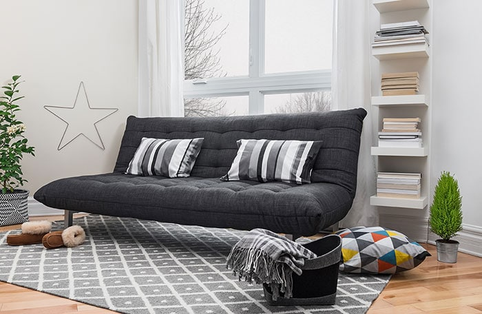 Black couch sitting on a rug to protect the floor.