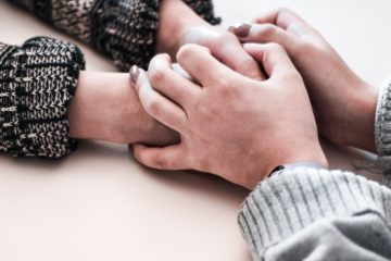 person in gray long sleeve shirt holding persons hand