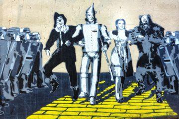 3 men and 2 women standing on yellow brick floor