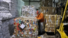 man in front of recycling blocks at recycle plant