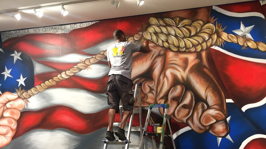 """Hamilton Glass paints in the details of the rope depicted in his mural """"Bound."""" (Courtesy: Virginia Museum of History and Culture)"""