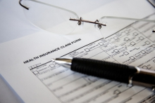 A zoomed in photograph of a health insurance claim form next to glasses and a pen.