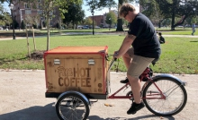 In Monroe Park, student Carter Bain rides the Free Hot Coffee Bike, which was designed to engage people in conversation about recovery.