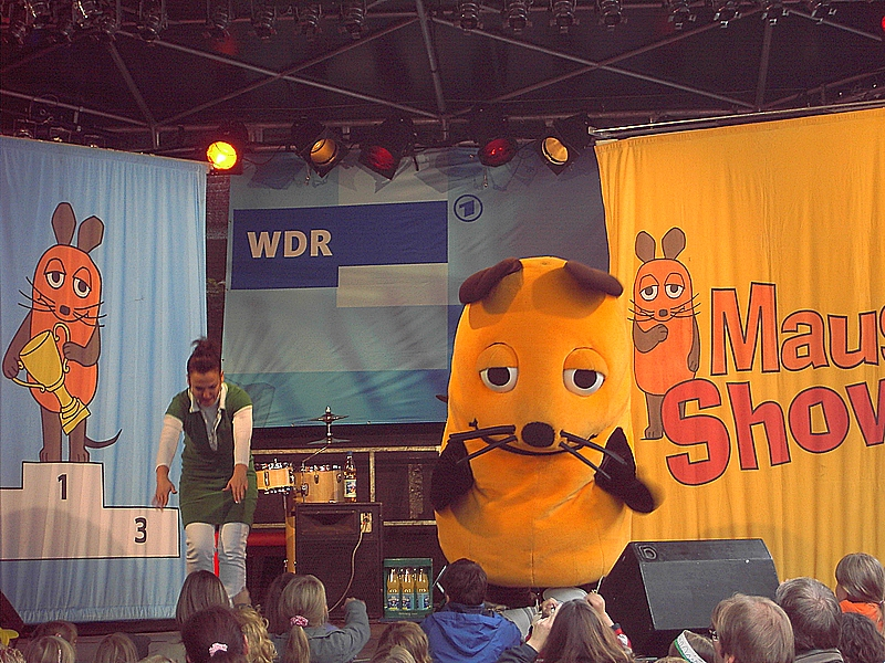 A person in a costume of a mouse on a stage in front of kids