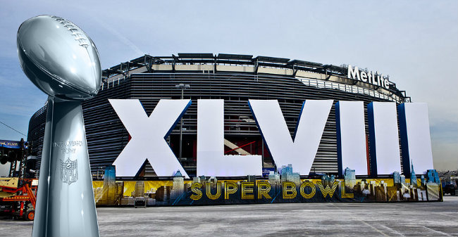 The Vince Lombardi Trophy super-imposed on the background of MetLife Stadium behind the Super Bowl XLVIII sign. (Photo source: WikiMedia Commons - JayJizzle and Anthony Quintano )