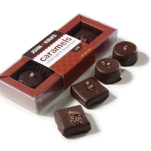 Two dark chocolate caramels and two lightly salted caramels in a clear plastic box with brown frame and wrapper