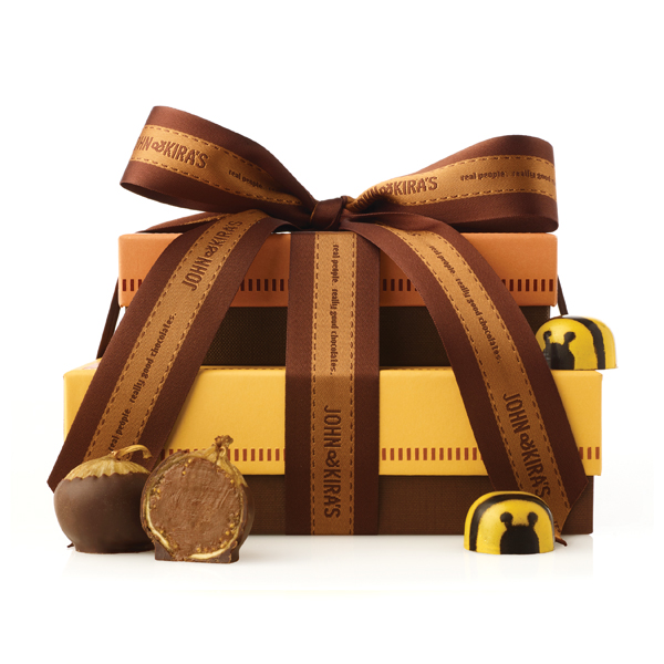 12 figs in a light brown box atop 16 honey caramel bees in a square yellow box tied with coordinating ribbon