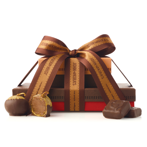six chocolate figs in a light brown box atop a dark brown 15pc every flavor box tied together with coordinating ribbon