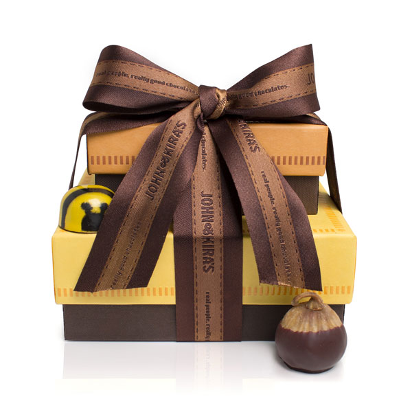 Six Chocolate dipped figs in an orange box atop nine Caramel Bees in a square yellow boutique box