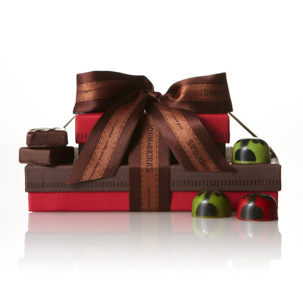 A red box of Ladybugs atop a 15 piece brown boutique box of chocolate ganache