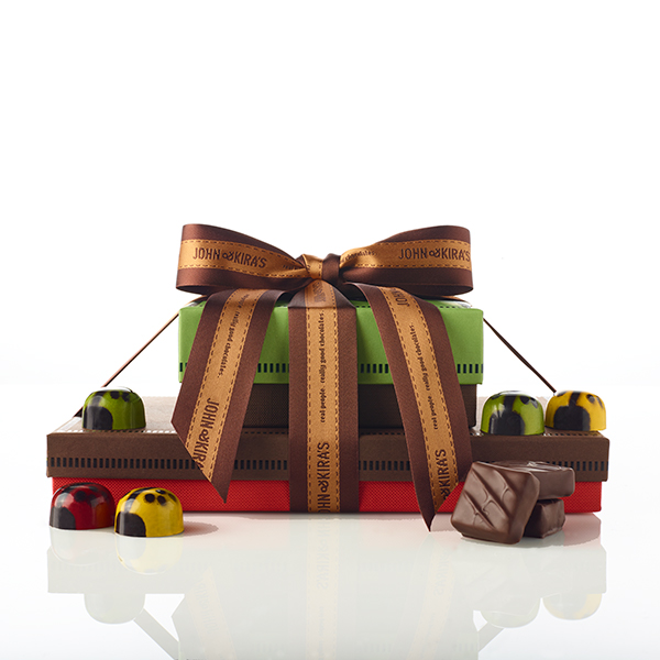 Nine assorted ladybugs in a green boutique box atop 28 pieces of our Every Flavor ganache in a brown boutique box