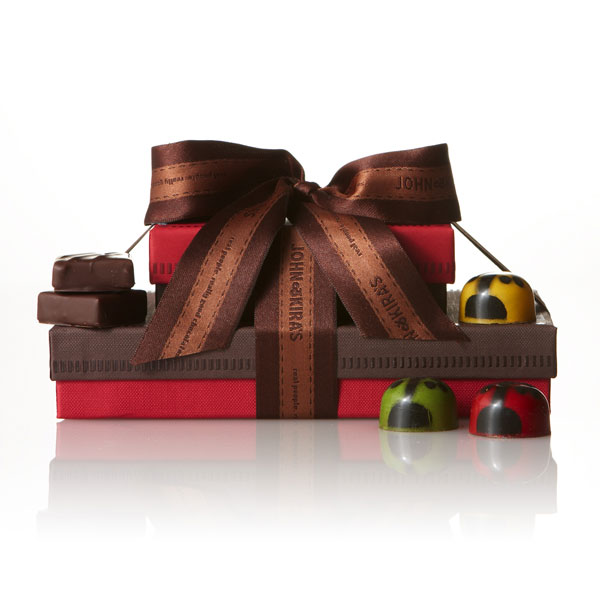 Six assorted ladybugs in a green boutique box atop fifteen pieces of our Every Flavor ganache in a brown boutique box