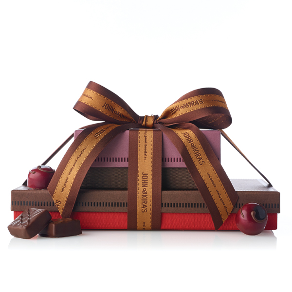 Square dark red boutique box of Cherries atop a 28 piece brown box with chocolate ganache
