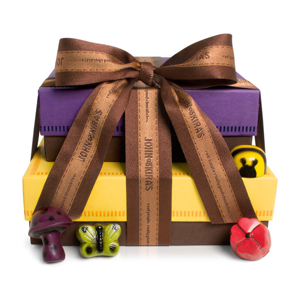 A dark purple square boutique box of enchanted forest chocolates atop a sixteen piece square yellow boutique box of honey caramel bees