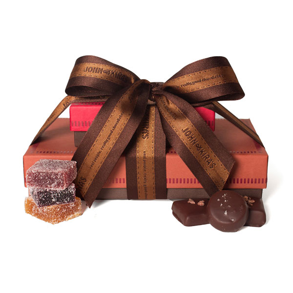 Six piece red box of Fruit Squares atop 15 pieces of Caramel in a brown boutique box