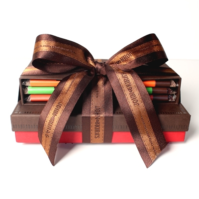 Mint, Orange Rosemary, and Chili Bars in a brown box set tied with ribbon atop 15 piece brown boutique box of Every Flavor Chocolates