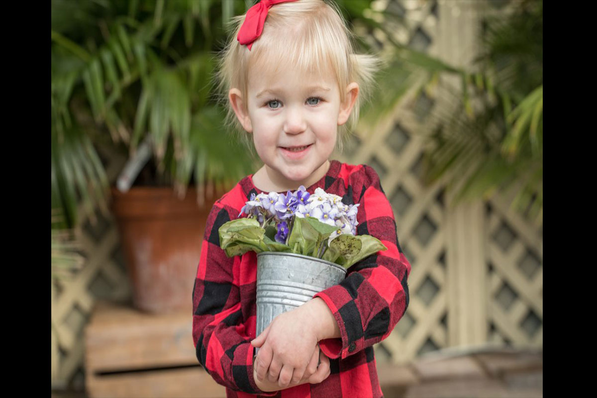 young girl with can of flowers