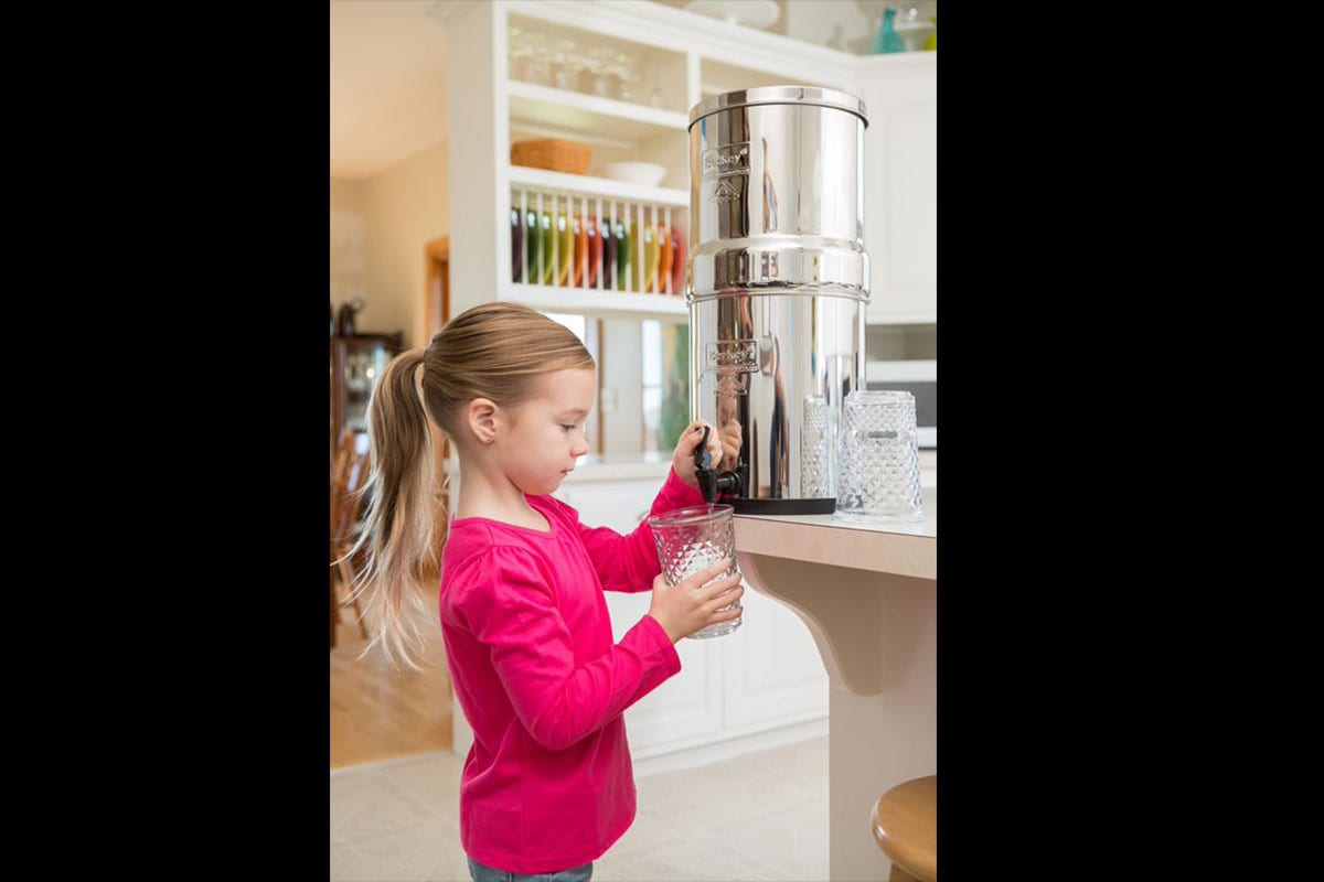 Young girl filling glass with water from a Berkey water filter
