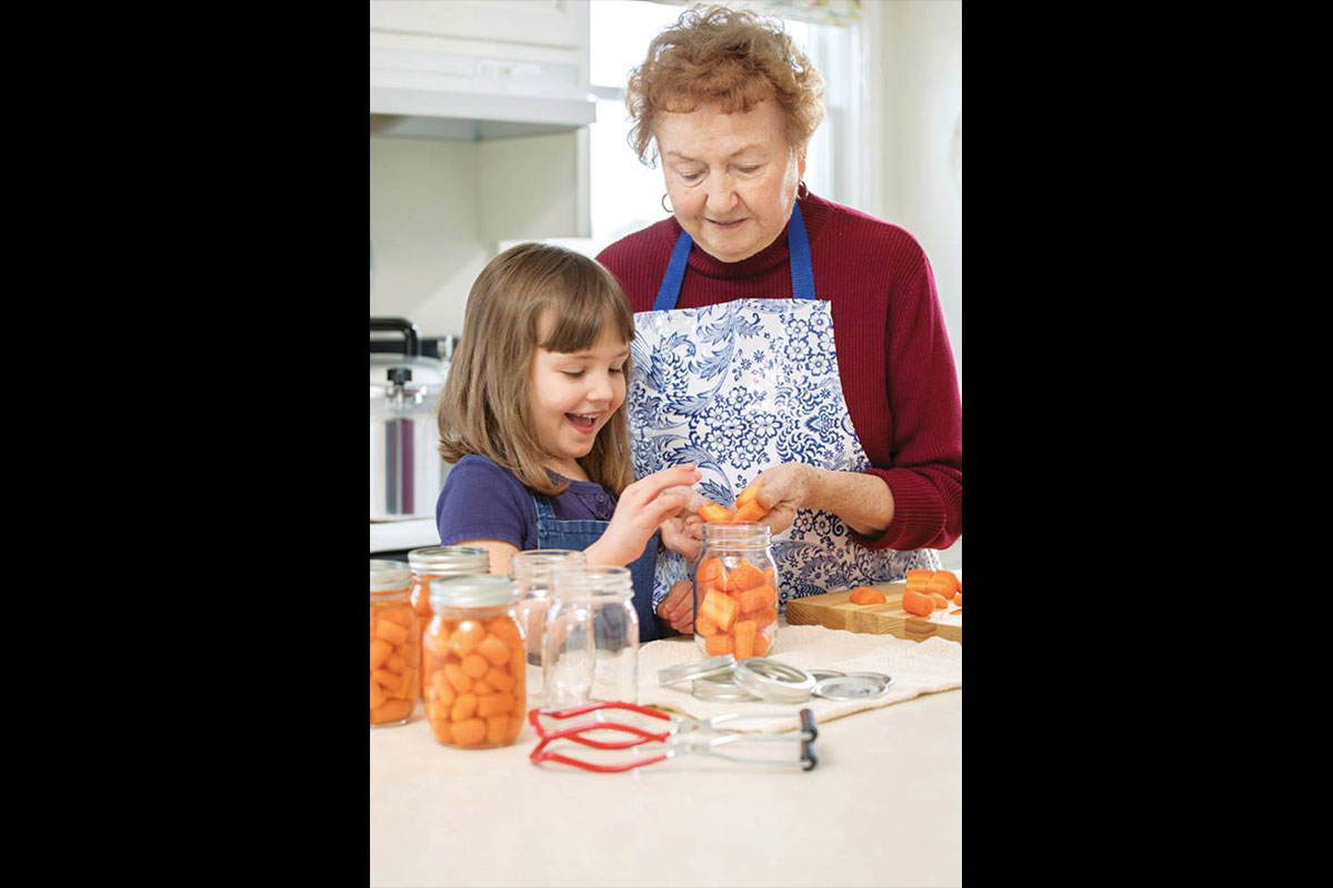 young girl helping her grandmother can food
