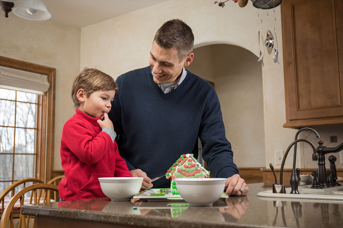 Young boy and his father decorating a gingerbread house