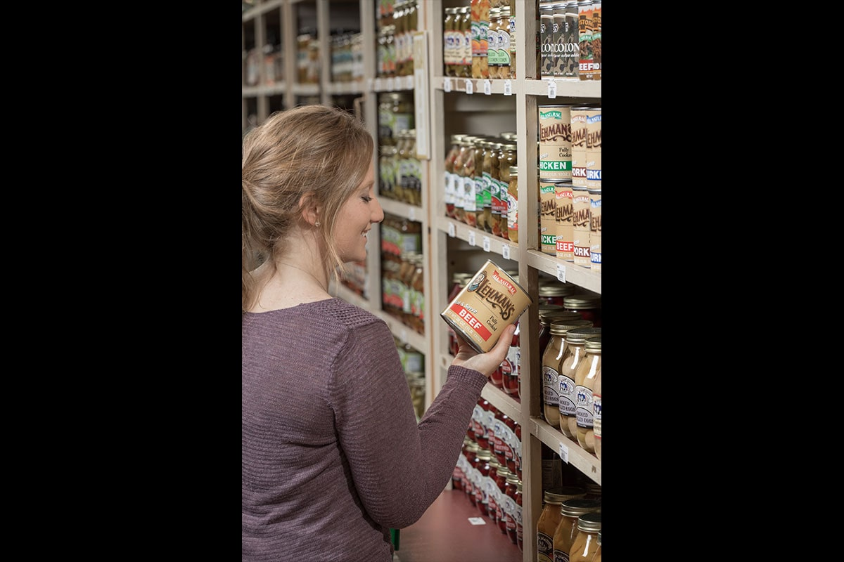 Woman browsing pantry stocked with canned goods from Lehman's