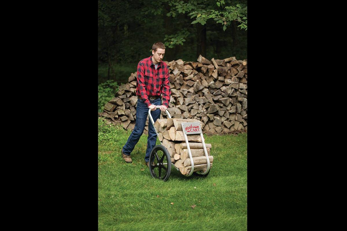 Man pushing an Amish-made cart full of chopped wood.
