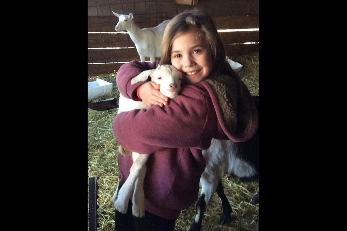 Young girl hugging a kid (baby goat)