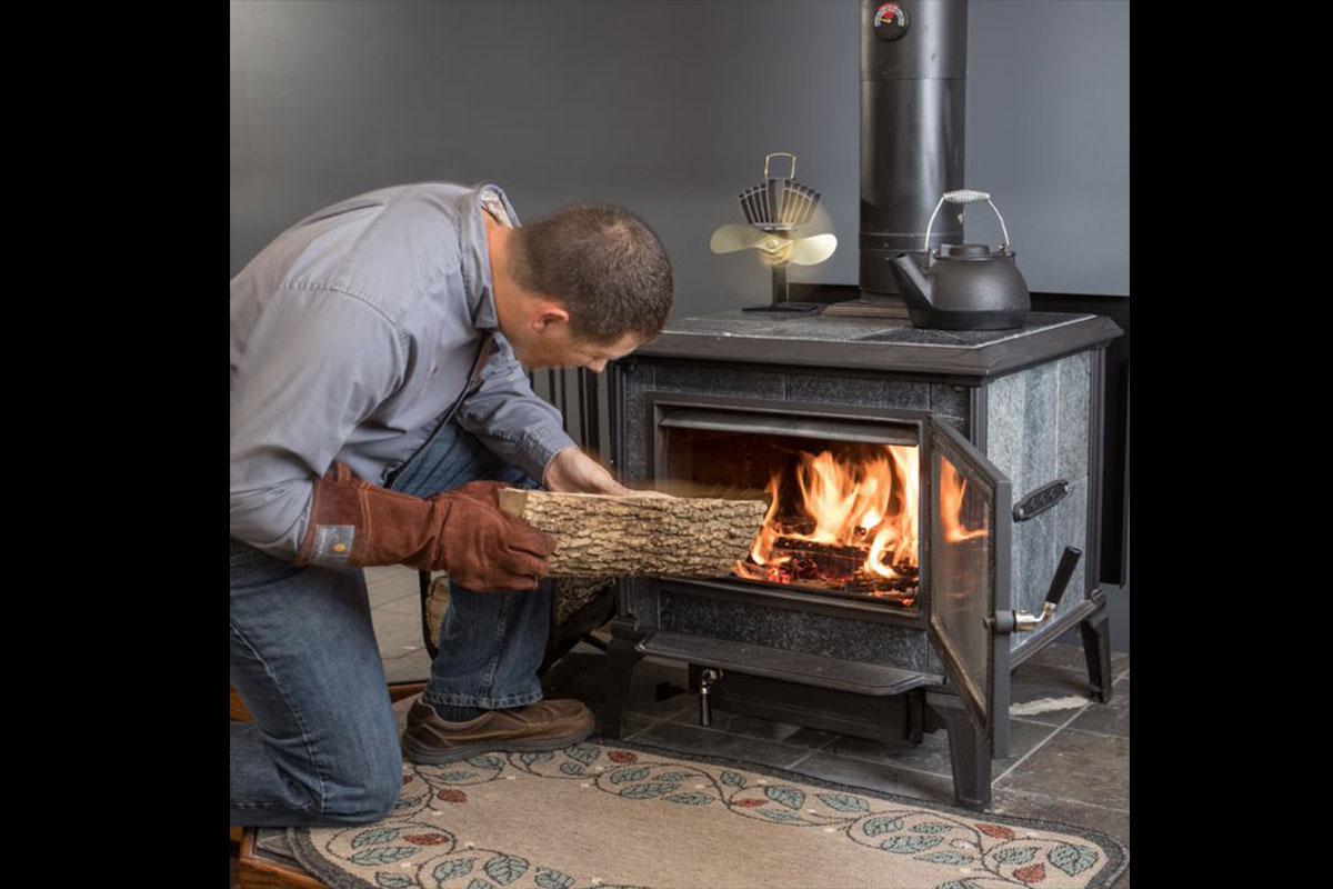 man feeding split log into fireplace