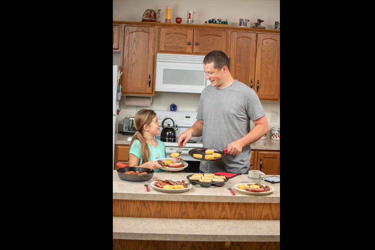 Man preparing traditional breakfast with his daughter on cast iron cookware.