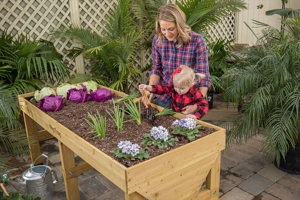 Woman gardening in a VegTrug elevated garden bed with her young daughter
