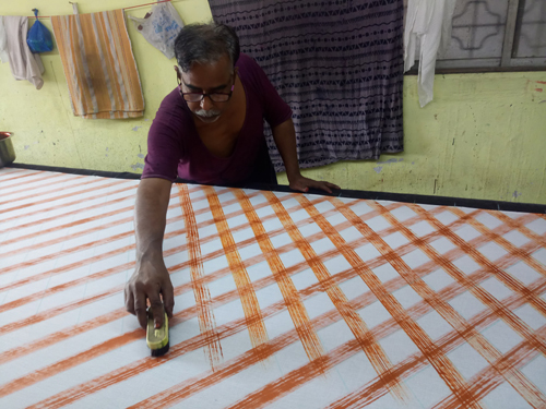 Artisan using a scrub brush to create a unique painted line on fabric.