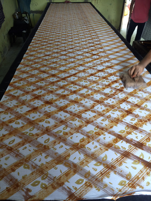 Artisan using scrub brush and paint to create a diagonal checkered pattern on cloth.