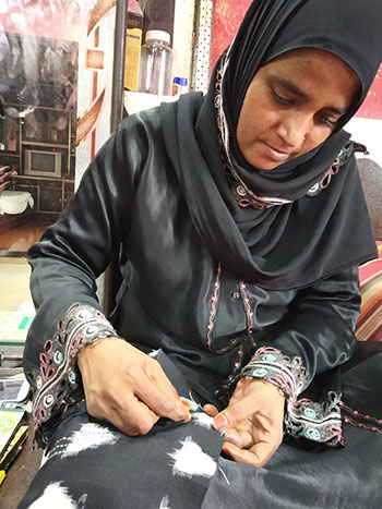 An artisan at home doing embroidery