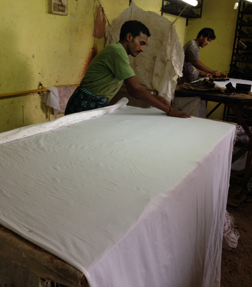 Artisan spreads fabric across a table in preparation for the application of wax.