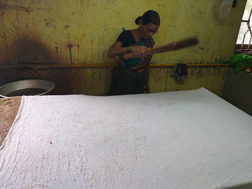 Drops of wax applied to fabric using a slender broom.