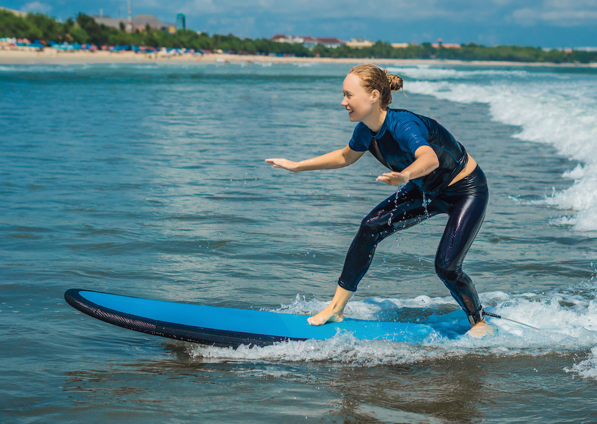 Joyful young woman beginner surfing with blue surf has fun on small sea waves 1200x853